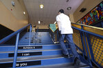 A school janitor walks up stairs inside Bothell High School, closed for the day, Thursday, Feb. 27, 2020, in Bothell, Wash. The suburban Seattle school was closed Thursday after a staffer's family member was placed in quarantine for showing symptoms of possibly contracting the new virus that started in China - an action health officials say is unnecessary. The school will be cleaned and disinfected on Thursday while students stay home. (AP Photo/Elaine Thompson)