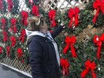 In this Saturday, Dec. 7, 2019 photo, Sandy Parsons looks over some Christmas wreaths for sale at her stand at the Capitol Market in Charleston, W.Va. Parsons never received her order of 350 trees this year from a North Carolina farm, citing a short supply. Instead, she was sent a few much-smaller trees to sell at her lot. Christmas trees are in tight supply again this year across the United States, depending upon location and seller, as the industry continues bouncing back from the Great Recession. (AP Photo/John Raby)
