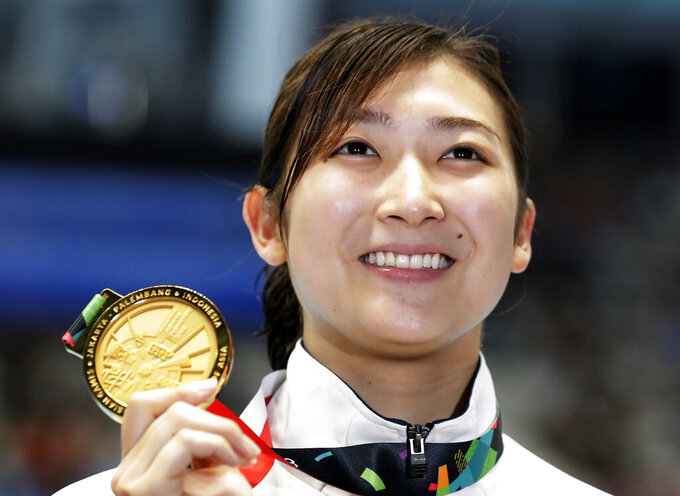 FILE - In this Aug. 24, 2018, file photo, Japan's Rikako Ikee holds up her gold medal after winning the women's 50m freestyle final during the swimming competition at the 18th Asian Games in Jakarta, Indonesia. Ikee was the star of the Asian Games two years ago, winning six gold medals in Jakarta in freestyle and butterfly and was billed as Japan's Olympics star in 2020. However, she was diagnosed with leukemia early in 2019 and has undergone a year of difficult treatment. The 20-year-old says she hopes to compete in the 2024 Paris Olympics.(AP Photo/Lee Jin-man, File)