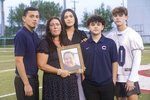 Karyn Arellano holds a photo of her husband Alan, while surrounded by her children Erick Hernandez, left, Alyssa Hernandez, Evan and A.J. Arellano, Thursday, Sept. 2, 2021, in Miami. Alan Arellano, 49, died after suffering a heart attack while being treated for COVID-19. Alan was a dedicated father, stressing education, work and love for family to his kids. (AP Photo/Marta Lavandier)