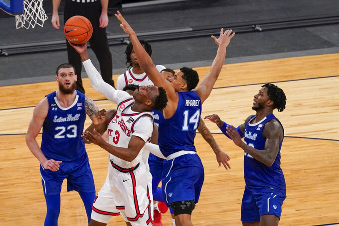 St. John's guard Rasheem Dunn (3) goes to the basket past Seton Hall guard Jared Rhoden (14) and forward Sandro Mamukelashvili (23) during the second half of an NCAA college basketball game in the quarterfinals of the Big East conference tournament, Thursday, March 11, 2021, in New York. (AP Photo/Mary Altaffer)