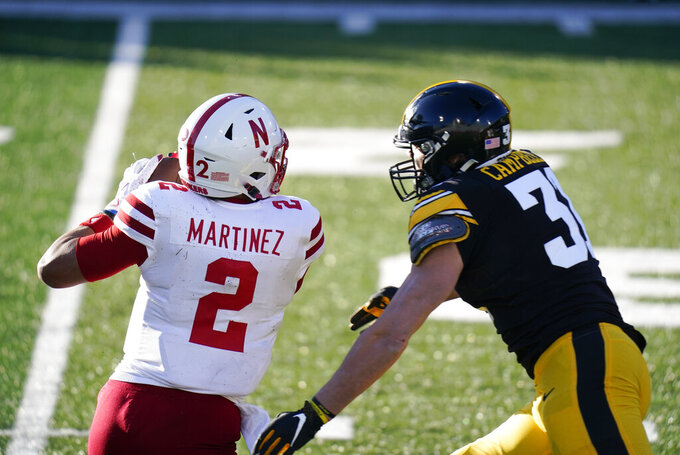 Iowa linebacker Jack Campbell, right, chases Nebraska quarterback Adrian Martinez (2) during the second half of an NCAA college football game, Friday, Nov. 27, 2020, in Iowa City, Iowa. Iowa won 26-20. (AP Photo/Charlie Neibergall)