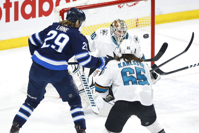 San Jose Sharks goaltender Aaron Dell (30) keeps his eyes on the puck as Winnipeg Jets' Patrik Laine (29) takes a swipe at it, while Sharks' Erik Karlsson (65) defends during the first period of an NHL hockey game Friday, Feb. 14, 2020, in Winnipeg, Manitoba. (John Woods/The Canadian Press via AP)