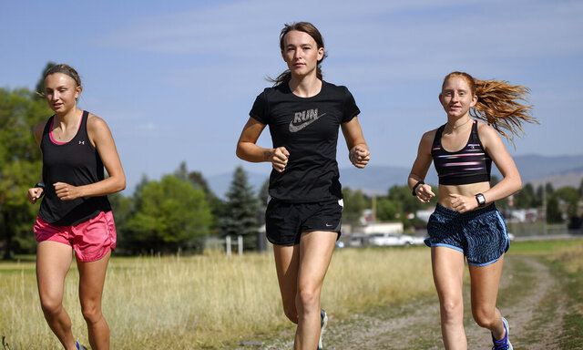 FILE - In this Aug. 15, 2019, file photo, is University of Montana cross country runner Juniper Eastwood, center, warming up with her teammates at Campbell Park in Missoula, Mont. Transgender kids would be banned from playing on school sports teams for the gender with which they identify under a GOP-backed bill that advanced Thursday, Jan. 21, 2021, in Montana. The proposed ban is personal for people like Eastwood, a transgender woman and former member of the University of Montana's track and field and cross-country running teams. She said the legislation