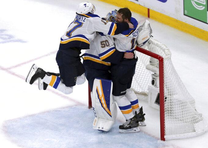 St. Louis Blues' Jaden Schwartz, left, and Brayden Schenn, right, mob goaltender Jordan Binnington, to celebrate their win over the Boston Bruins in Game 7 of the NHL hockey Stanley Cup Final, June 12, 2019, in Boston. (AP Photo/Charles Krupa)