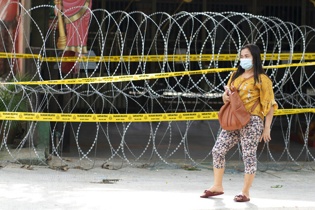 A woman stands near the barbed wire outside a locked down building during the movement control order in Kuala Lumpur, Malaysia, Monday, April 20, 2020. The Malaysian government issued a restricted movement order to the public till April 28, to help curb the spread of the new coronavirus. (AP Photo/Vincent Thian)