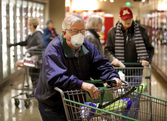 Shopper Merlin Smith, 82, of Edina navigates the aisles of Lunds and Byerlys during an early morning hour devoted to older shoppers and shoppers with health conditions Thursday, March 19, 2020, in Edina, Minn. Smith was also shopping for his wife who has heart issues and was home. Some supermarket retailers across the world and Twin Cities are creating an early bird shopping time from 7-8 a.m. for older shoppers to protect them from COVID-19 and coronavirus.  (Merlin Smith/Star Tribune via AP)