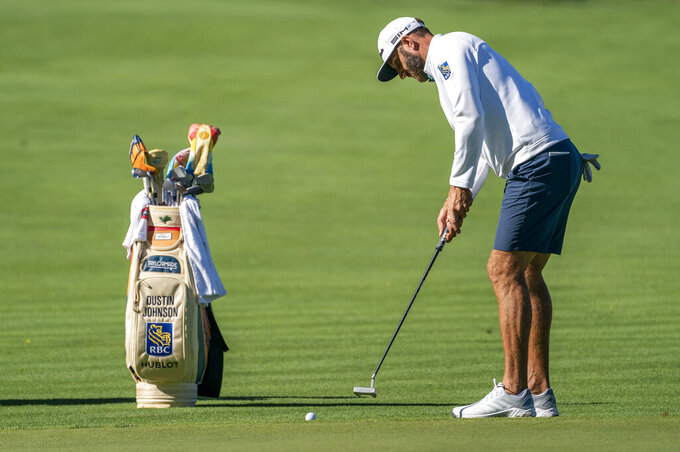 Defending champion Dustin Johnson hits onto the eighth green during professional-amateur team play ahead of the Travelers Championship golf tournament at TPC River Highlands, Wednesday, June 23, 2021, in Cromwell, Conn. (AP Photo/John Minchillo)