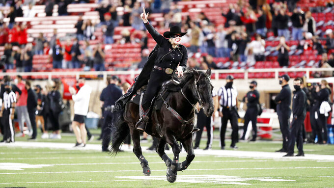 Texas Tech's Masked Rider Cameron Hekkert rides before an NCAA college football game against Oklahoma, Saturday, Oct. 31, 2020, in Lubbock, Texas. (AP Photo/Mark Rogers)