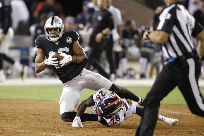 FILE - In this Sept. 9, 2019, file photo, Oakland Raiders wide receiver Tyrell Williams tumbles over Denver Broncos cornerback Isaac Yiadom (26) after making a reception during the first half of an NFL football game in Oakland, Calif. It will be the end of an era of sorts this weekend in Oakland. Not that anyone figures to be mourning what should be the final NFL game ever played on a field with infield dirt, especially the players who have had to deal with the bad footing, ripped jerseys, scraped arms and legs and hard falls onto a surface with no cushion.(AP Photo/Ben Margot, File)
