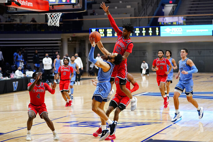 Villanova's Caleb Daniels (14) tries to get a shot past St. John's Vince Cole (15) during the first half of an NCAA college basketball game, Tuesday, Feb. 23, 2021, in Villanova, Pa. (AP Photo/Matt Slocum)