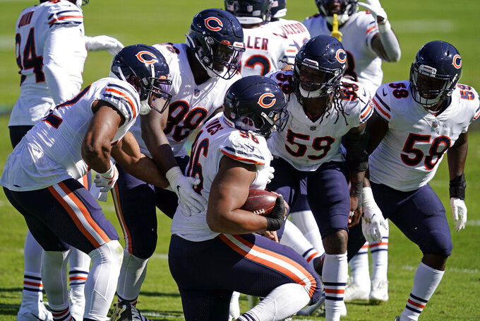 Chicago Bears defensive end Akiem Hicks (96) is congratulated by teammates following a turnover during the second half of an NFL football game against the Carolina Panthers in Charlotte, N.C., Sunday, Oct. 18, 2020. (AP Photo/Brian Blanco)