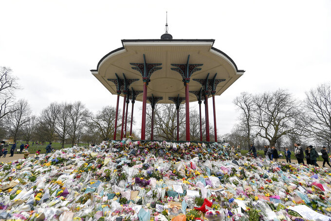 """FILE - In this file photo dated Saturday, March 20, 2021, floral tributes and messages surround the bandstand on Clapham Common in London after the nearby disappearance of Sarah Everard.  A U.K. police watchdog said Tuesday March 30, 2021, that officers did not behave """"in a heavy-handed manner"""" when they broke up a vigil for Sarah Everard, who disappeared while walking home in London and was later found murdered.  (AP Photo/Alberto Pezzali, FILE)"""