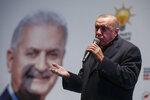 Turkey's President Recep Tayyip Erdogan addresses the supporters of his ruling Justice and Development Party, AKP, at a rally in Istanbul, late Tuesday, March 19, 2019, ahead of local elections scheduled for March 31, 2019. An image of AKP's mayoral candidate for Istanbul, Binali Yildirim, is seen in the background. (AP Photo/Emrah Gurel)