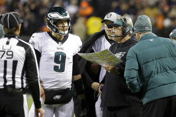 Philadelphia Eagles quarterback Nick Foles (9) talks to head coach Doug Pederson during the second half of an NFL wild-card playoff football game against the Chicago Bears Sunday, Jan. 6, 2019, in Chicago. (AP Photo/David Banks)
