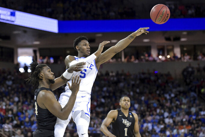 Duke forward RJ Barrett (5) passes to a teammate, away from Central Florida forward Chad Brown, left, during the first half of a second-round game in the NCAA men's college basketball tournament Sunday, March 24, 2019, in Columbia, S.C. Duke won 77-76. (AP Photo/Sean Rayford)
