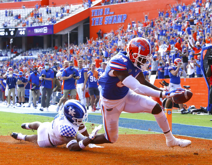 FILE - Florida tight end Kyle Pitts (84) scores a touchdown during an NCAA college football game against Kentucky in Gainesville, Fla., in this Saturday, Nov. 28, 2020, file photo. The Dallas Cowboys signed their star quarterback to a long-term deal, which means they won't be in the market at that position with the 10th overall pick in the NFL draft. The most likely candidate as another CeeDee Lamb, the receiver still on the board at No. 17 a year ago, is Florida tight end Kyle Pitts, who is projected to go several spots before the Cowboys. Then again, so was Lamb. (Brad McClenny/The Gainesville Sun via AP, FIle)