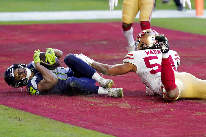 Seattle Seahawks wide receiver Tyler Lockett scores a touchdown as San Francisco 49ers middle linebacker Fred Warner (54) defends during the second half of an NFL football game, Sunday, Jan. 3, 2021, in Glendale, Ariz. (AP Photo/Ross D. Franklin)