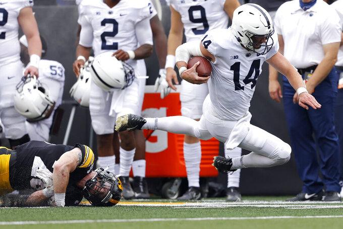 Iowa defensive back Jack Koerner (28) trips up Penn State quarterback Sean Clifford (14) on a run in the first half of an NCAA college football game, Saturday, Oct. 9, 2021, in Iowa City, Iowa. (AP Photo/Matthew Putney)