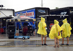 Race fans walk through the garage area during a weather delay before the NASCAR Cup Series auto race at Daytona International Speedway, Saturday, July 6, 2019, in Daytona Beach, Fla. (AP Photo/Phelan Ebenhack)