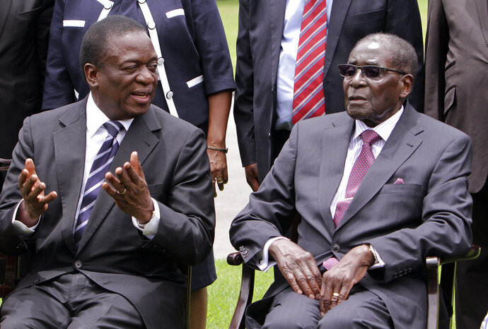 FILE - In this Friday, Dec, 12, 2014 file photo Emmerson Mnangagwa, left, then Vice President of Zimbabwe chats with Zimbabwean President Robert Mugabe after the swearing in ceremony at State House in Harare. Mugabe, the former leader of Zimbabwe forced to resign in 2017 after a 37-year rule whose early promise was eroded by economic turmoil, disputed elections and human rights violations, has died. He was 95. (AP Photo/Tsvangirayi Mukwazhi, File)