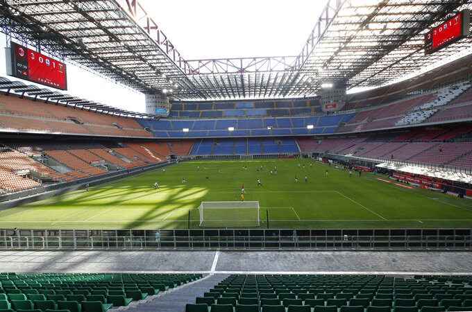 """FILE - In this Sunday, March 8, 2020 file photo, a view of the empty San Siro stadium during the Serie A soccer match between AC Milan and Genoa, in Milan, Italy. The Italian soccer players' association rejected a proposal from Serie A clubs Monday to reduce salaries by a third if the season does not resume as """"unmanageable."""" The guideline austerity measure was agreed on by 19 of the 20 clubs, the Italian league announced, with Juventus not included because it already finalized a deal with its players to relieve financial pressure on the eight-time defending champion amid the coronavirus pandemic. (AP Photo/Antonio Calanni, File)"""