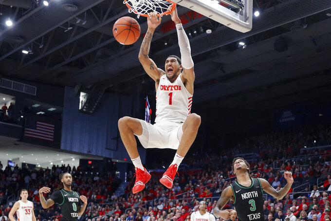 FILE - In this Dec. 17, 2019, file photo, Dayton's Obi Toppin (1) dunks as North Texas' Javion Hamlet (3) looks on during the second half of an NCAA college basketball game in Dayton, Ohio. Kansas finished the season No. 1 in The Associated Press college basketball poll, Wednesday, March 18, 2020. Dayton was third behind breakout stars Jalen Crutcher and Obi Toppin, the leading candidate for national player of the year. (AP Photo/John Minchillo, File)