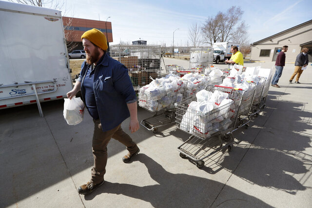 In this Tuesday, March 17, 2020, photo Patrick Minor loads food onto a delivery truck at the Des Moines Area Religious Council food pantry in Des Moines, Iowa. With the new coronavirus leaving many people at least temporarily out of work, food banks and pantries across the U.S. are scrambling to meet an expected surge in demand, even as older volunteers have been told to stay home and calls for social distancing have complicated efforts to package and distribute food. (AP Photo/Charlie Neibergall)