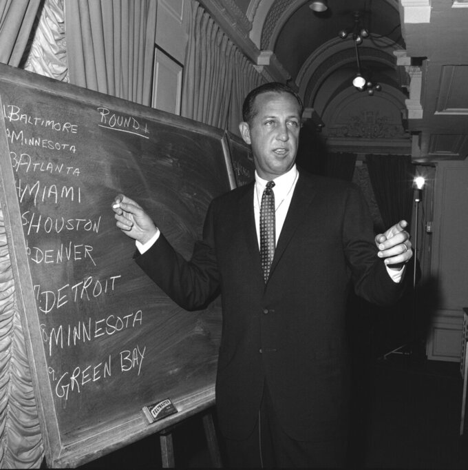 "FILE - In this March 14, 1967, file photo, Pete Rozelle, professional football commissioner, works at on a blackboard at a New York City hotel during the first round of the combined National Football League (NFL) - American Football league (AFL) football player draft. ESPN approached NFL Commissioner Pete Rozelle in 1980 offering to broadcast the proceedings of the NFL Draft from the New York Sheraton. Rozelle couldn't fathom why ESPN boss Chet Simmons made the offer. ""Pete thought Chet was out of his mind,"" said former ESPN vice president John Wildhack. ""But Pete said, 'Let's try it."" (AP Photo/Jacob Harris, File)"
