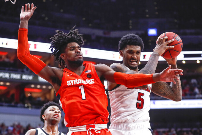 Louisville forward Malik Williams (5) grabs a rebound away from Syracuse forward Quincy Guerrier (1) during the second half of an NCAA college basketball game Wednesday, Feb. 19, 2020, in Louisville, Ky. Louisville won 90-66. (AP Photo/Wade Payne)