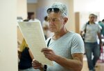 A man reads a ballot at a polling station during a parliamentary election in Kiev, Ukraine, Sunday, July 21, 2019. Ukrainians are voting in an early parliamentary election in which the new party of President Volodymyr Zelenskiy is set to take the largest share of votes. (AP Photo/Evgeniy Maloletka)