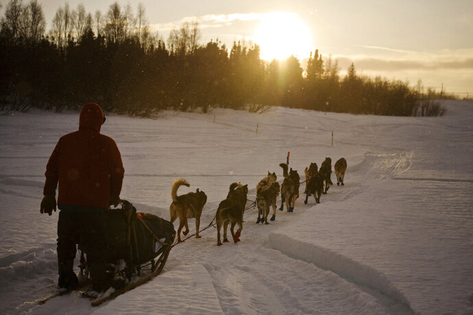 FILE - In this March 8, 2018 file photo Musher Ramey Smyth approaches Shageluk, Alaska, as rain falls and some sun hits the area during the Iditarod Trail Sled Dog Race. PETA is the biggest critic of the world's most famous sled dog race, but new Iditarod CEO Rob Urbach has started discussions with the animal rights group and plans a sit-down meeting with PETA Thursday, Oct. 17, 2019, in Los Angeles. (Marc Lester/Anchorage Daily News via AP, File)