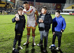 Catalans Dragons Israel Folau has his photo taken with young fans after the Super League rugby match between Catalans Dragons and Castleford Tigers at Stade Gilbert Brutus in Perpignan, France, Saturday, Feb. 15, 2020. (AP Photo/Joan Monfort)