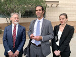 FILE - In this Nov. 20, 2019, file photo, Scott Warren, center, of Ajo, Ariz., celebrates with his attorneys Amy Knight, right, and Greg Kuykendall outside court in Tucson, Ariz., after being acquitted of two counts of harboring in a case that garnered international attention. (AP Photo/Astrid Galvan, File)
