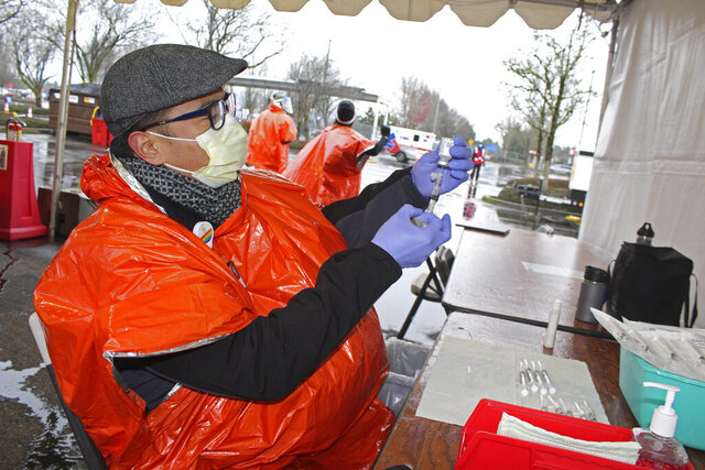 In this photo provided by Oregon Health & Science University, Oliver Pelayo, an OHSU registered nurse, prepares vaccine doses during a drive-thru clinic held in a parking lot at the Portland International Airport in Portland, Ore., on Jan. 24, 2021. An advisory committee in Oregon that provides recommendations to the governor and public health authorities about which groups to prioritize next for the COVID-19 vaccine is tackling what role race should play in those decisions as tensions around urgent questions of equity and vaccine access bubble up nationwide. (Erik Robinson/Oregon Health & Science University via AP)