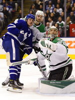 Toronto Maple Leafs center Auston Matthews (34) and Dallas Stars center Jason Dickinson (18) and goaltender Ben Bishop (30) all look up toward the puck during the second period of an NHL hockey game Thursday, Feb. 13, 2020, in Toronto. (Frank Gunn/The Canadian Press via AP)
