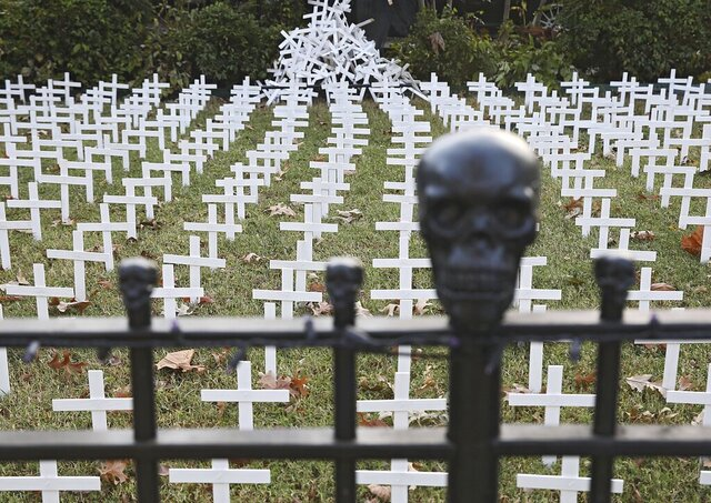 Toby Gregory's yard that is adorned with 1,006 white crosses to represent Oklahoma deaths due to COVID-19, Wednesday, Oct. 14, 2020, in Tulsa, Okla. Gregory was able to keep up with the state death toll until last week, and then it became too many. He says he doesn't have the room or supplies to keep up with the current death toll, but will do about 50 more crosses. (Mike Simons/Tulsa World via AP)
