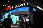 FILE - In this Oct. 31, 2019, file photo, attendees walk past a display for 5G services from Chinese technology firm Huawei at the PT Expo in Beijing. U.S. President Joe Biden has nearly doubled the list of Chinese companies whose shares are off-limits to U.S. investors in the latest sign he is not softening Washington's stance toward Beijing. Telecoms equipment maker Huawei Technologies, China's big state-owned telecoms companies and China National Offshore Oil Corp. are on the new list of 59 companies. (AP Photo/Mark Schiefelbein, File)