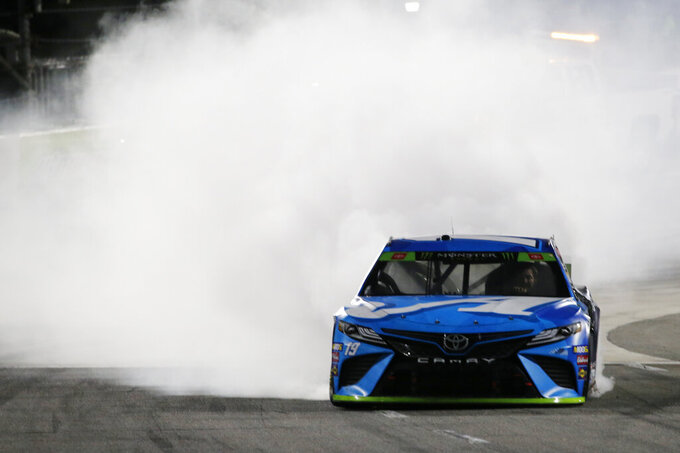 Martin Truex Jr. (19) does a burnout as he celebrates after winning a NASCAR Cup Series race at Martinsville Speedway in Martinsville, Va., Sunday, Oct. 27, 2019. (AP Photo/Steve Helber)