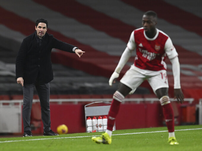 Arsenal's manager Mikel Arteta, left, gives instructions to his players during the English Premier League soccer match between Arsenal and Manchester United at the Emirates stadium in London, Saturday, Jan. 30, 2021. (Andy Rain/Pool via AP)