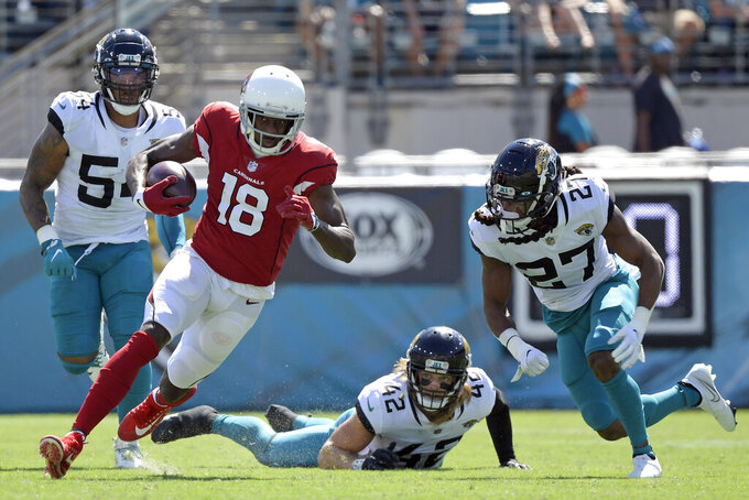 Arizona Cardinals wide receiver A.J. Green runs after a reception past Jacksonville Jaguars outside linebacker Damien Wilson, left, defensive back Andrew Wingard (42) and cornerback Chris Claybrooks (27) during the second half of an NFL football game, Sunday, Sept. 26, 2021, in Jacksonville, Fla. (AP Photo/Phelan M. Ebenhack)