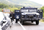 Kosovo special police with armored vehicles stand on the road near the northern Kosovo border crossing of Jarinje, Monday, Sept. 20, 2021. Tensions have soared on the border between Kosovo and Serbia as Pristina authorities started implementing a rule to remove Serbian license plates from cars entering Kosovo. Kosovo special police with armored vehicles were deployed Monday on the tense border as hundreds of Kosovo Serbs reportedly drove there in their cars to protest the move. (AP Photo/Bojan Slavkovic)