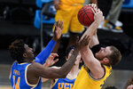 Michigan forward Austin Davis grabs a rebound over UCLA forward Kenneth Nwuba, left, during the second half of an Elite 8 game in the NCAA men's college basketball tournament at Lucas Oil Stadium, Tuesday, March 30, 2021, in Indianapolis. (AP Photo/Michael Conroy)