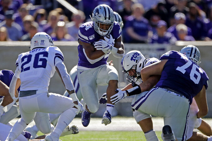 Kansas State running back James Gilbert (34) runs between TCU defensive end Wyatt Harris, right, and safety Vernon Scott (26) during the first half of an NCAA college football game Saturday, Oct. 19, 2019, in Manhattan, Kan. (AP Photo/Charlie Riedel)