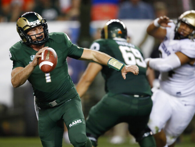 FILE--In this Friday, Aug. 31, 2018, file photograph, Colorado State quarterback K.J. Carta-Samuels rolls out to pass under pressure during the second half of an NCAA college football game against Colorado in Denver. Colorado won 45-13. Carta-Samuels and the Rams will host Arkansas on Saturday. (AP Photo/David Zalubowski, File)