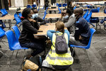 People sit at a table in a shelter for residents after flooding in Angleur, Province of Liege, Belgium, Friday July 16, 2021. Severe flooding in Germany and Belgium has turned streams and streets into raging torrents that have swept away cars and caused houses to collapse. (AP Photo/Valentin Bianchi)