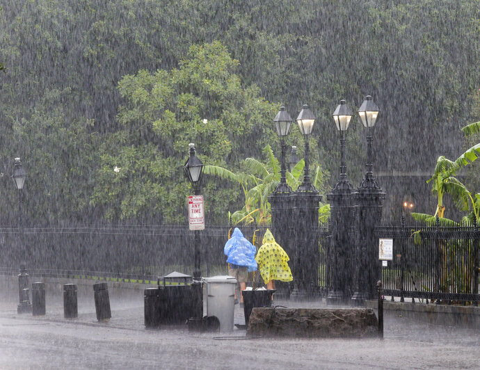 People walk on a street during a downpour at the French Quarter in New Orleans, Sunday, July 14, 2019. Tropical Depression Barry dumped rain as it slowly swept inland through Gulf Coast states Sunday, sparing New Orleans from a direct hit but stoking fears elsewhere of flooding, tornadoes, and prolonged power outages. (David Grunfeld/The Advocate via AP)