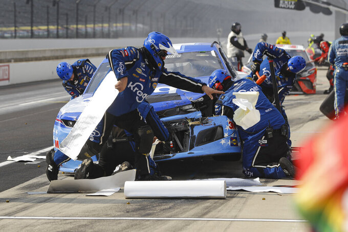 Crew members for the car driven by Ricky Stenhouse Jr. work on the car after a crash in the pit area during a NASCAR Cup Series auto race at Indianapolis Motor Speedway in Indianapolis, Sunday, July 5, 2020. (AP Photo/Darron Cummings)