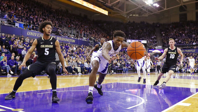 Washington forward Nahziah Carter, center, reaches for a loose ball as Colorado guard D'Shawn Schwartz (5) and forward Alexander Strating (10) watch during the first half of an NCAA college basketball game Saturday, Feb. 23, 2019, in Seattle. (AP Photo/Ted S. Warren)