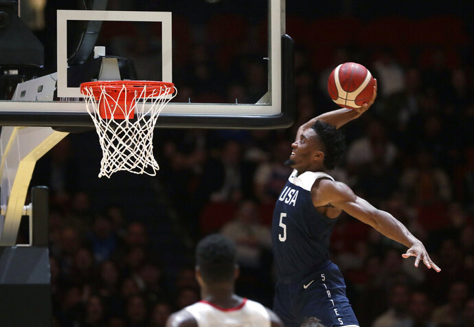 United States' Donovan Mitchell jumps up to dunk the ball against Canada  during their exhibition basketball game in Sydney, Australia, Monday, Aug. 26, 2019. (AP Photo/Rick Rycroft)